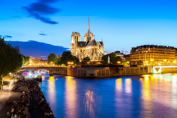 Notre Dame De Paris at night and the seine river in Paris, France.
