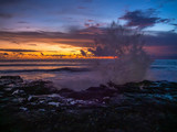 Splashing waves of stones on the background of multi-colored clouds at sunset. Ko Phangan.Thailand.