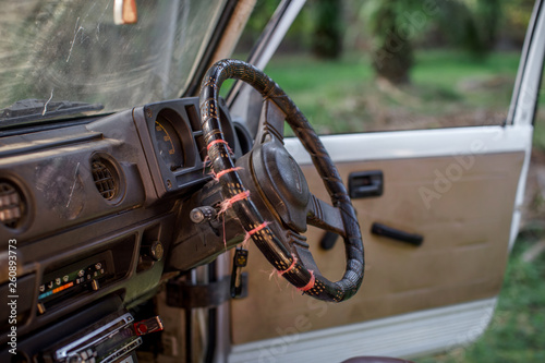 Close-up background view of the car steering wheel (driver's cabin), blurred by sunlight and use, often used in agriculture or in rubber plantations, oil palms