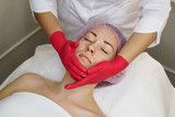 Hands of beautician make face massage girl. Regenerative therapy in spa salon.