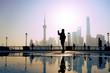Quadro traveler take a photo of morning activity at the bund, huangpu riverside,  shanghai city view background