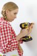 Quadro Woman drilling in wall