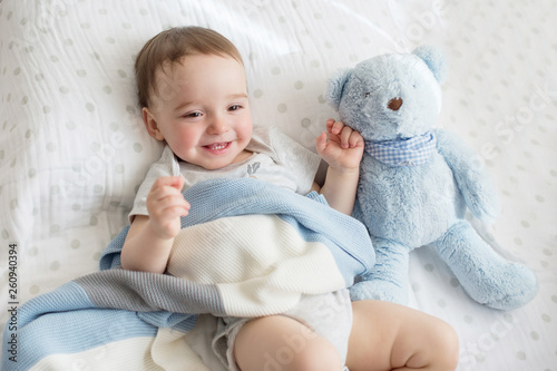 Little boy is playing on the bed (with a book or a teddy bear).