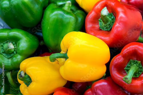 Red and yellow and Green sweet peppers. Pile Three sweet peppers on a wooden background, Cooking vegetable salad . Colorful sweet bell peppers, natural background. - 260946187