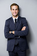 canvas print picture - smiling young businessman, on grey
