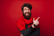 Leinwanddruck Bild - Cheerful bearded man with red scarf pointing away over red wall background