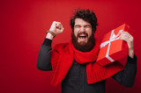 Portrit of excited bearded man, holding a gift box, while celebrating over red background