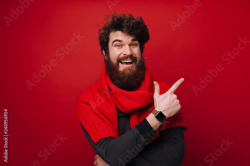 Leinwanddruck Bild Cheerful bearded man with red scarf pointing away over red wall background
