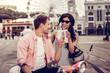 Leinwandbild Motiv Joyful positive couple cheering with their drinks