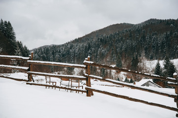 A winter landscape, top of the mountaine village, little fence, and forrest