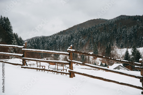 canvas print picture A winter landscape, top of the mountaine village, little fence, and forrest