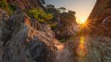 Scenery spanish rocky coast at sunrise. Sun shines from rocks on sea bay in Costa Brava
