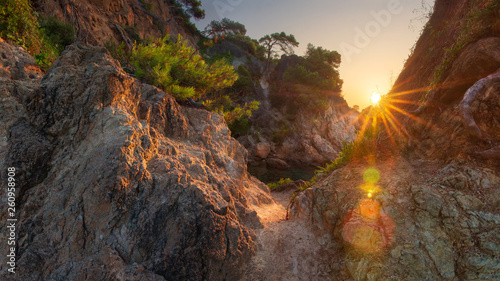 Scenery spanish rocky coast at sunrise. Sun shines from rocks on sea bay in Costa Brava