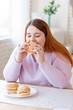 Leinwandbild Motiv Nice plump woman eating a tasty burger