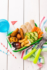 Picnic lunch box with chicken, fries, tortilla and vegetables