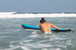 Woman surfer is trying to get into line up trough waves during her surfing workout