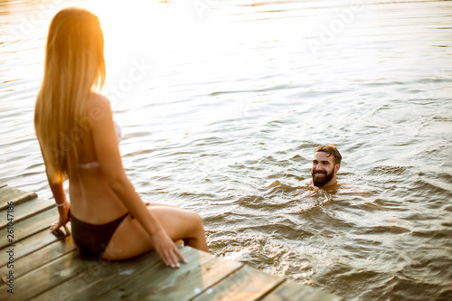 Leinwanddruck Bild Young couple enjoying while woman sitting on pier and man swimming in the lake