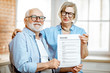 Portrait of a happy senior couple holding resume document indoors. Concept of work in older age