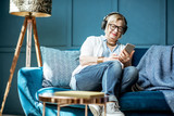 Senior woman dressed casually listening to the music with headphones and phone on the couch at home