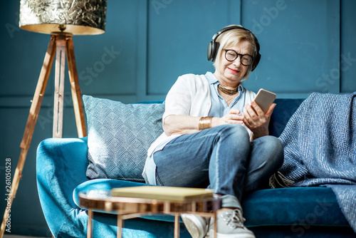 Senior woman dressed casually listening to the music with headphones and phone on the couch at home - 261050528