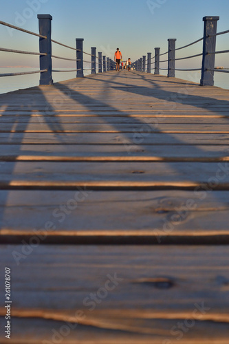 Son and daddy in a beautiful sunset in a wooden pier © MaizaRitomy