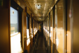 Long empty sunlit corridor of passenger train in warn colors. Train car interior. Concept of traveling and journey.