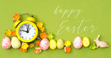 congratulations on Easter. Beautiful Easter scene. alarm clock, eggs with flowers and Easter rabbit. Easter holiday background, spring season. top view