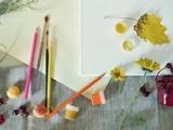 Empty white canvas, art materials, fresh flowers, decor on a light background, top view, summer season
