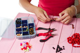 Jewelry making. Making bracelet of colorful beads. Female hands with a tool on a pink background.
