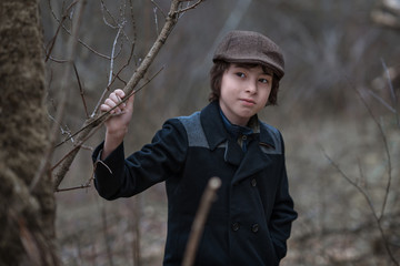 Portrait of a boy in a coat and cap against the background of nature.