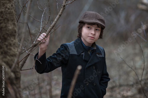 canvas print picture Portrait of a boy in a coat and cap against the background of nature.