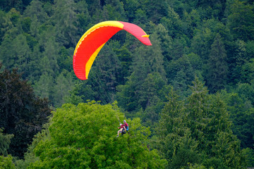 Tandem paragliders flying in the cloudy sky