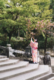 Kyoto, Japan - April 3, 2018: Young woman wearing traditional Japanese Kimono in public park