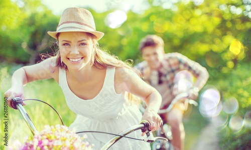Happy young couple cycling through the park - 261151160