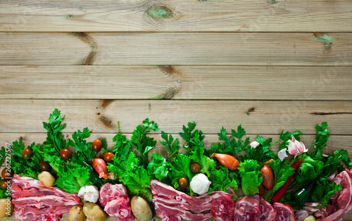 Pieces of fresh lamb meat on a wooden desk with  vegetables © JackF