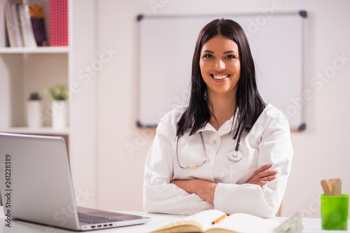 canvas print picture Portrait of young happy doctor in her office.