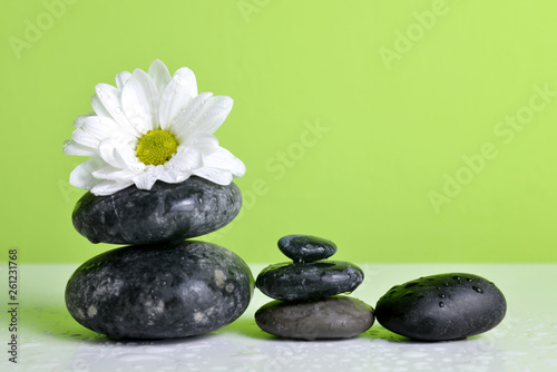 Leinwandbild Motiv Zen pebbles and white flower on table. Spa and healthcare concept.