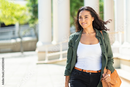 Young proud woman walking on street