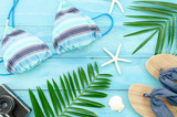 Flat lay summer background with plam branches, starfish and slippers on wooden planks background - 261242549