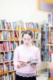 girl of 13 years old choosing   book in   library.