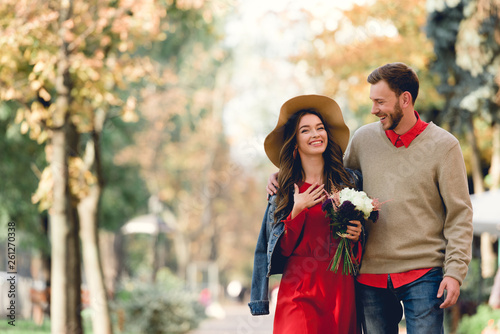 Leinwandbild Motiv happy man looking at girlfriend in hat smiling while holding flowers