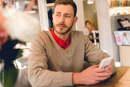 canvas print picture handsome bearded man holding smartphone in cafe