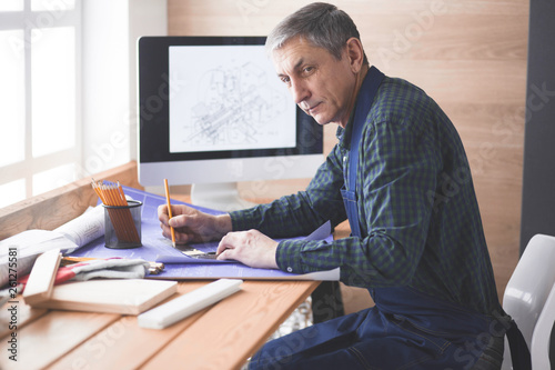 Engineer carpenter working on laptop and sketching project