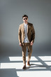 good-looking stylish man in beige suite and sunglasses standing in sunlight on grey