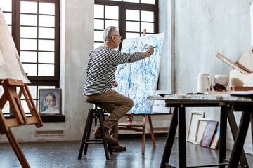 Talented bearded artist sitting on chair and painting on canvas