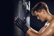Side view of boxer holding punching bag with closed eyes on black