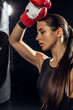 Tired boxer with ponytail standing near punching bag on black