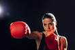 Focused female boxer in red boxing gloves training and looking away on black