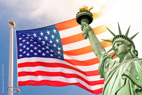 Statue of Liberty, sunny sky and USA flag background