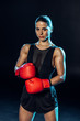 Strong boxer in red gloves looking at camera on black